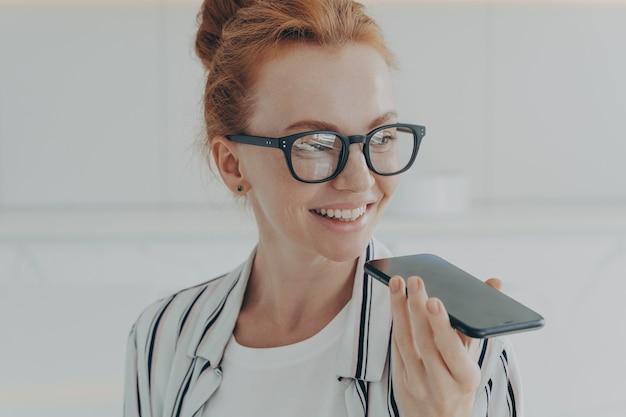 Портрет счастливой веселой рыжеволосой женщины в очках, держащей мобильный телефон с записью аудиосообщения