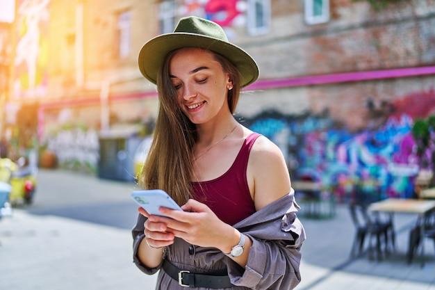 Портрет счастливой веселой улыбающейся красивой милой радостной молодой миллениальной девушки, использующей телефон на открытом воздухе