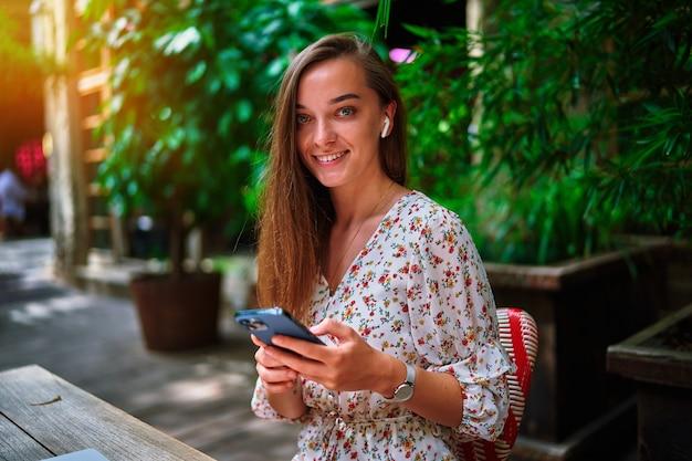Портрет счастливой веселой улыбающейся красивой милой жизнерадостной молодой миллениальной девушки в беспроводных наушниках и использующей телефон в кафе