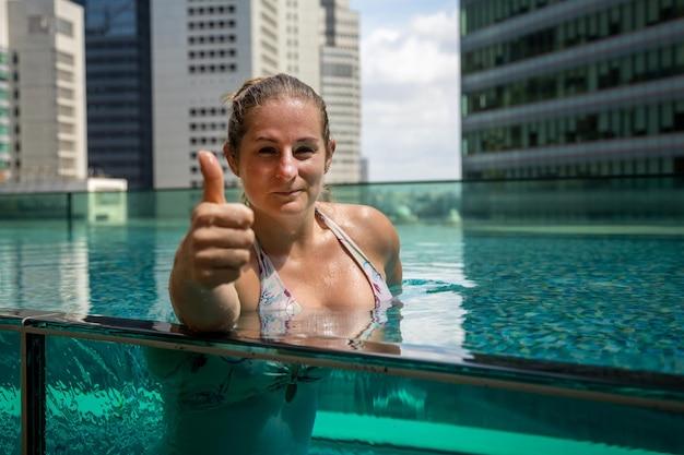 Портрет счастливой веселой улыбающейся женщины, расслабляющейся в бассейне и показывающей большие пальцы руки вверх