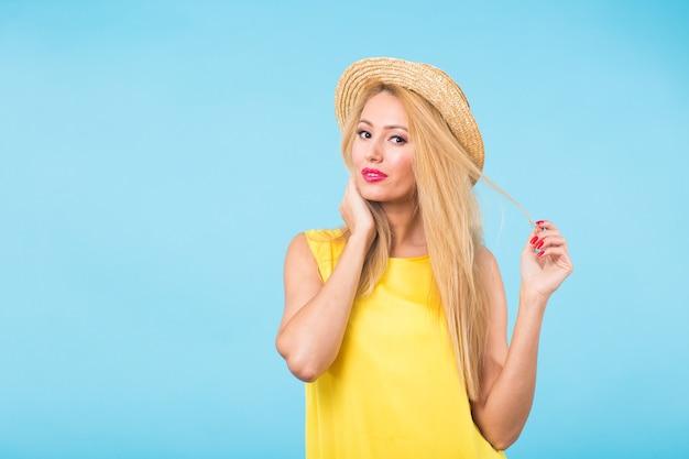 コピースペースと青い壁に幸せな陽気な笑顔の若い美しいブロンドの女性の肖像画