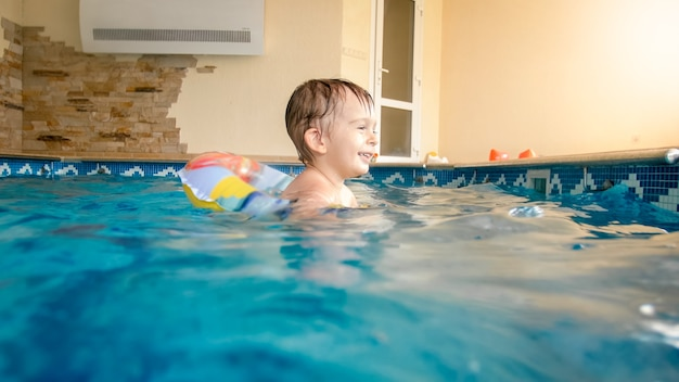 Портрет счастливого веселого мальчика-малыша, играющего с надувным пляжным мячом и красочным кольцом в крытом бассейне в доме Premium Фотографии