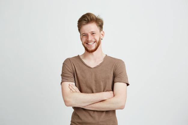 Портрет счастливый веселый молодой человек с бородой, улыбаясь со скрещенными руками.