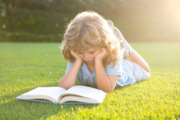 공원에서 책과 함께 행복 한 아이 소년의 초상화. 어린이 조기 교육. 어린 아이는 정원에서 책을 읽었습니다. 여름 방학 숙제입니다. 미취학 아동 야외입니다. 초등학교에서 온 귀여운 소년.