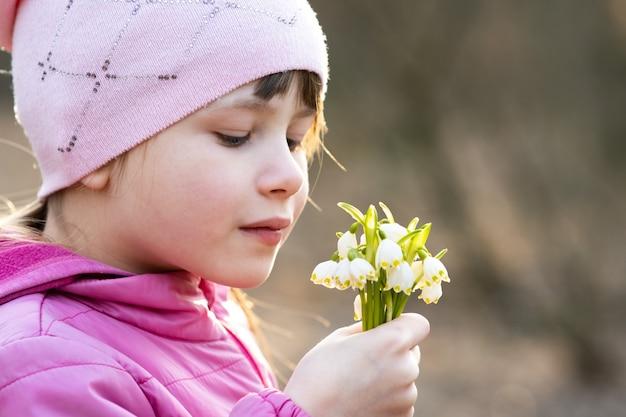 春先のスノードロップの花の束を屋外で保持している幸せな子の女の子の肖像画。