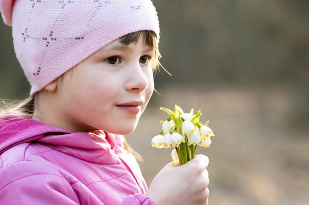Портрет счастливой девочки ребенка, держащей букет ранних весенних подснежников, цветет.