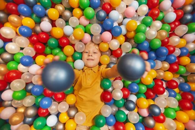 Портрет счастливого ребенка, лежащего среди цветных шаров и подбрасывающего шары вверх