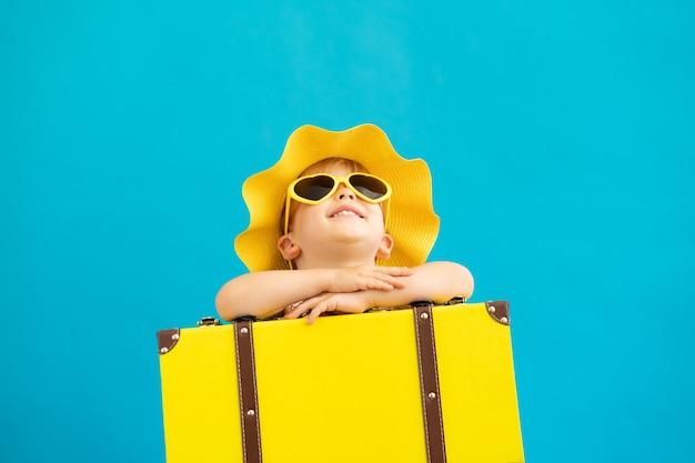 青い壁に黄色のスーツケースを持つ幸せな子の肖像画。