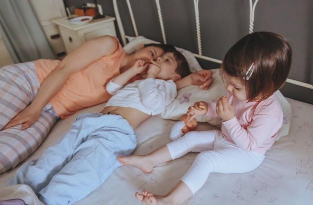 Портрет счастливых детей, едящих печенье в постели с матерью расслабленным утром. концепция семейного досуга в выходные дни.