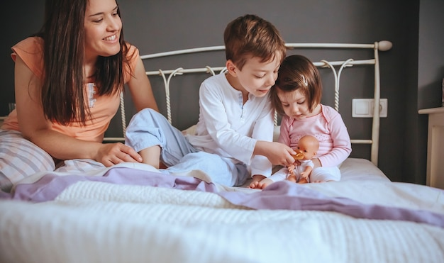 Портрет счастливых детей, кормящих куклу с печеньем, сидя в постели с их матерью расслабленным утром. концепция семейного досуга в выходные дни.