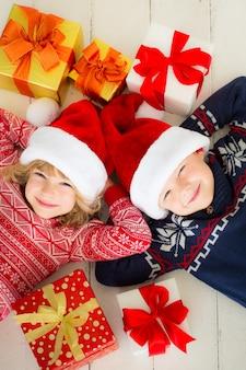 크리스마스 선물 상자가 있는 행복한 아이들의 초상화. 집에서 즐거운 시간을 보내는 두 아이