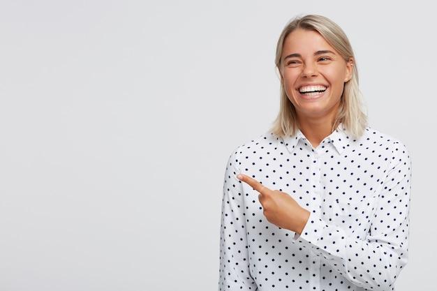 幸せな自信を持って金髪の若い女性の肖像画は笑顔で白い壁に隔離された指で横を指している水玉シャツを着ています