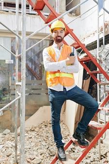 Портрет счастливого уверенного подрядчика в ярко-оранжевом жилете и каске, стоящего на лестнице в строящемся здании с рацией в руках