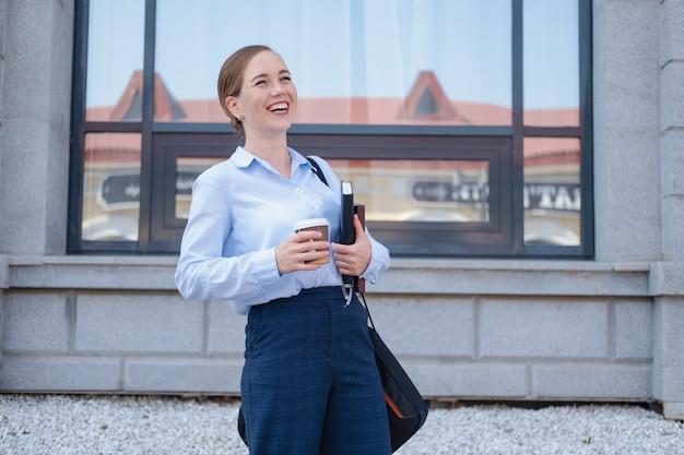 행복하고 자신감 있는 젊은 비즈니스 여성의 초상화는 커피를 마시고, 노트북과 노트북, 책을 들고 도시를 걷습니다. 일하러 가다. 고품질 사진