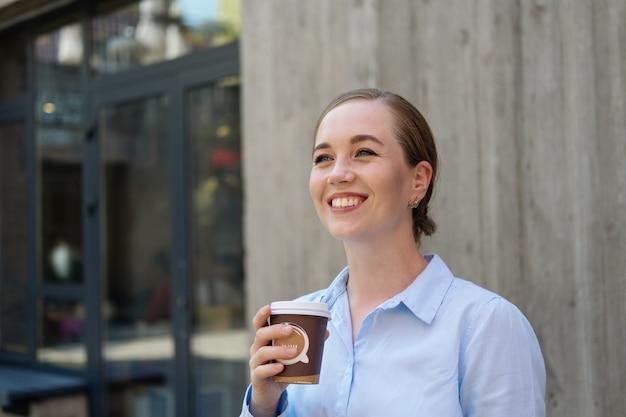 야외 도시에서 커피를 마시는 행복한 자신감 있는 젊은 비즈니스 여성의 초상화. 고품질 사진