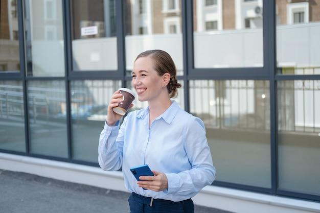선글라스를 끼고 자신감 넘치는 젊은 비즈니스 여성의 초상화, 야외 도시에서 커피를 마시며 전화를 타자. 고품질 사진