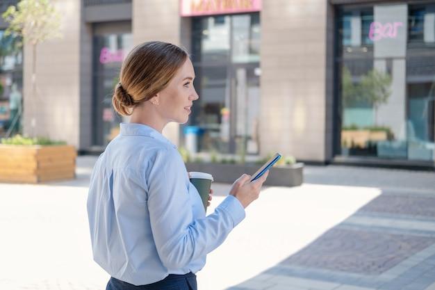 선글라스를 쓴 자신감 넘치는 젊은 비즈니스 여성의 초상화, 야외에서 커피를 마시며 전화를 타이핑합니다. 점심 시간. 고품질 사진