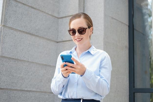 선글라스를 쓴 자신감 넘치는 젊은 비즈니스 여성의 초상화, 야외 도시에 서서 전화를 하고 있습니다. 고품질 사진
