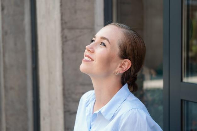 행복 한 자신감 젊은 비즈니스 여자의 초상화, 도시에 앉아. 꿈을 꾸고 하늘을 봅니다. 긴장을 풀고 인생을 즐기십시오. 성공 개념입니다. 고품질 사진
