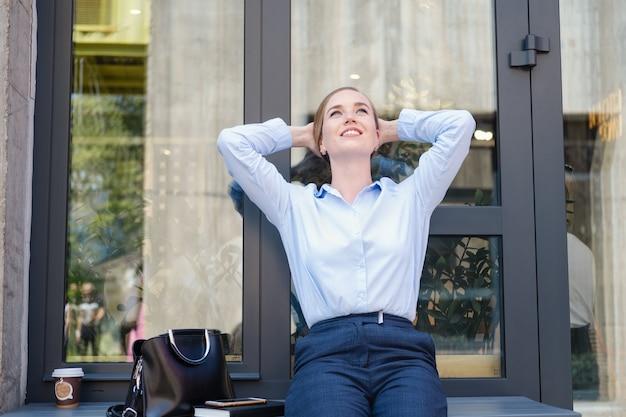 행복하고 자신감 있는 젊은 비즈니스 여성의 초상화, 커피와 노트북, 책이 있는 도시에 앉아 있습니다. 긴장을 풀고 인생을 즐기십시오. 성공 개념입니다. 고품질 사진