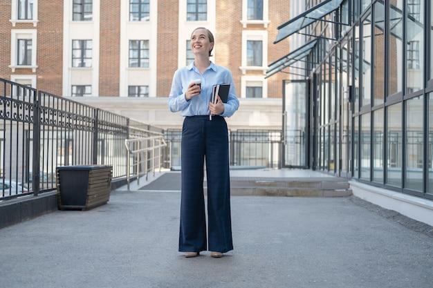 행복하고 자신감 있는 젊은 비즈니스 여성의 초상화, 커피와 책이 있는 도시에 서 있습니다. 일하러 가다. 고품질 사진