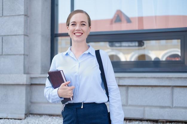 행복하고 자신감 있는 젊은 비즈니스 여성의 초상화는 도시에 노트북과 노트북, 책을 들고 서 있습니다. 일하러 가다. 고품질 사진