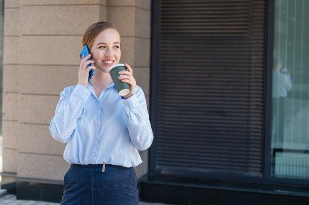 도시 야외에서 커피 스탠드를 마시는 동안 전화 통화를 하는 행복하고 자신감 있는 젊은 비즈니스 여성의 초상화. 고품질 사진