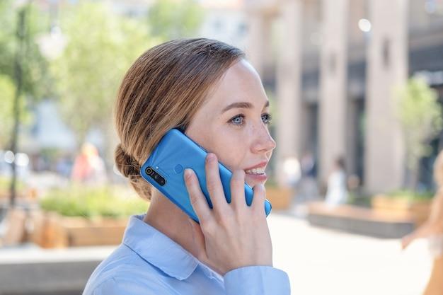 도시 야외에 서 있는 동안 전화 통화를 하는 행복한 자신감 있는 젊은 비즈니스 여성의 초상화. 밀레니얼의 삶입니다. 고품질 사진