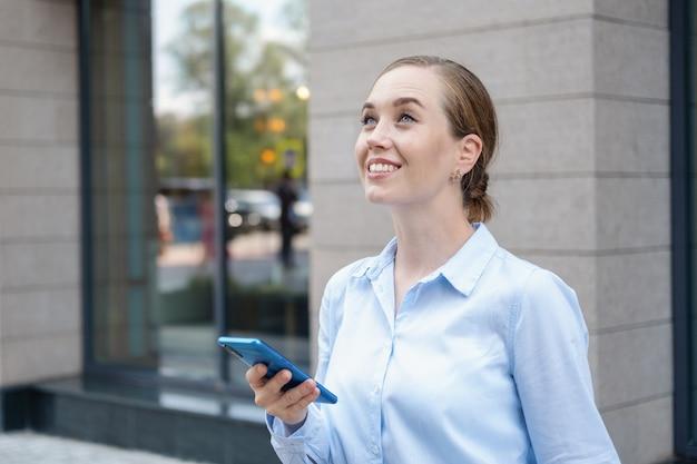 꿈을 꾸는 동안 전화로 타이핑을 하는 행복한 자신감 있는 젊은 비즈니스 여성의 초상화, 야외 도시에서 걸어보세요. 고품질 사진
