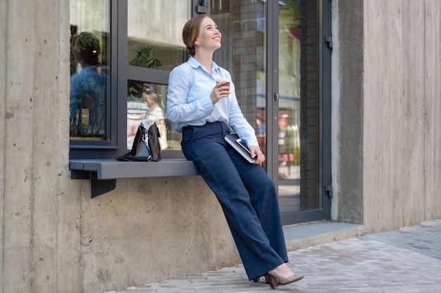 도시 야외에서 책을 마시는 행복한 자신감 있는 젊은 비즈니스 여성의 초상화. 고품질 사진