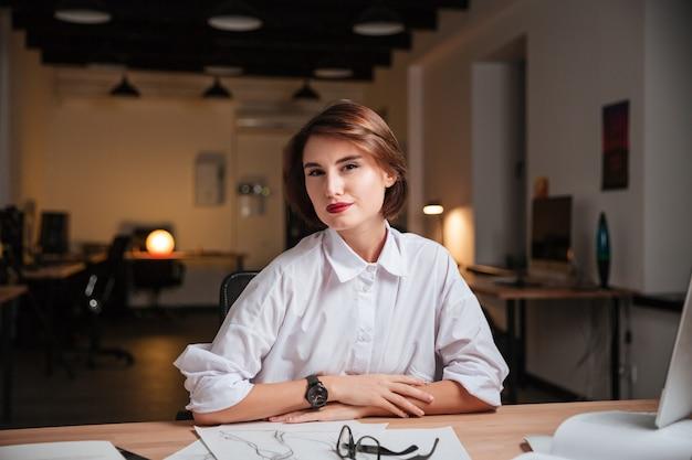 オフィスで幸せな自信を持って若い女性のファッションデザイナーの肖像画