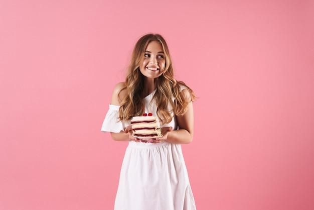 脇を見て、ピンクの壁に隔離されたケーキの一部を保持している白いドレスを着て幸せな混乱した女性の肖像画