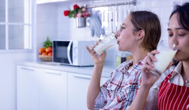 Портрет счастливой пары, пьющей молоко во время завтрака на кухне