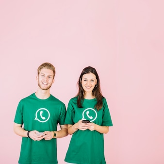 Portrait of happy couple in green whatsapp t-shirt holding smartphone