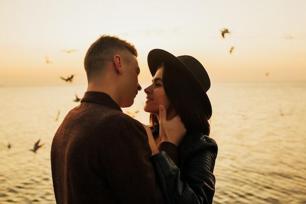 세련된 클래식 옷을 입은 사랑에 행복한 커플의 초상화는 바다 근처의 아름다운 여름 일몰 동안 감각적으로 포옹하고 있습니다.