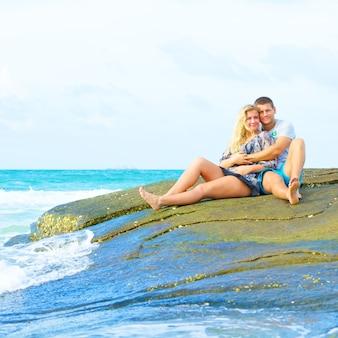 夏の日にビーチに座っている愛の幸せなカップルの肖像画