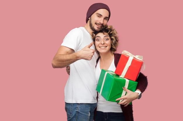캐주얼한 스타일로 서서 포옹하고 두 권투 선물을 들고 엄지손가락과 이빨 미소를 보여주는 행복한 친구 커플의 초상화는 기념일을 축하합니다. 절연, 실내, 스튜디오 촬영, 분홍색 배경