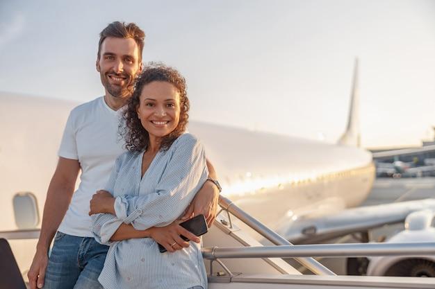 해질녘 비행기에 탑승할 준비를 하고 야외에서 함께 서 있는 동안 흥분해 보이는 남녀 관광객의 행복한 커플의 초상화. 휴가, 라이프 스타일, 여행 개념