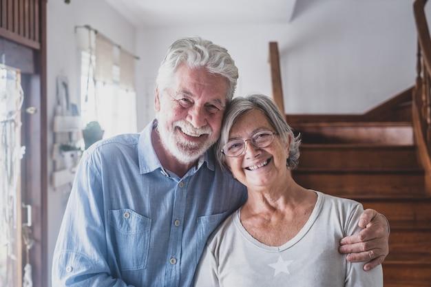 행복한 부부 노인들의 초상화는 함께 껴안고, 카메라를 바라보며, 성숙한 아내와 남편을 사랑하며 집에서 가족 사진에 포즈를 취한 건강한 장난기 가득한 미소를 짓고 있습니다.