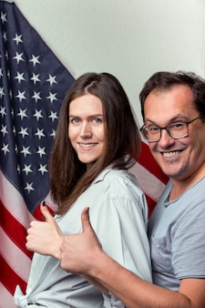 米国旗の背景に幸せなカップルの肖像画