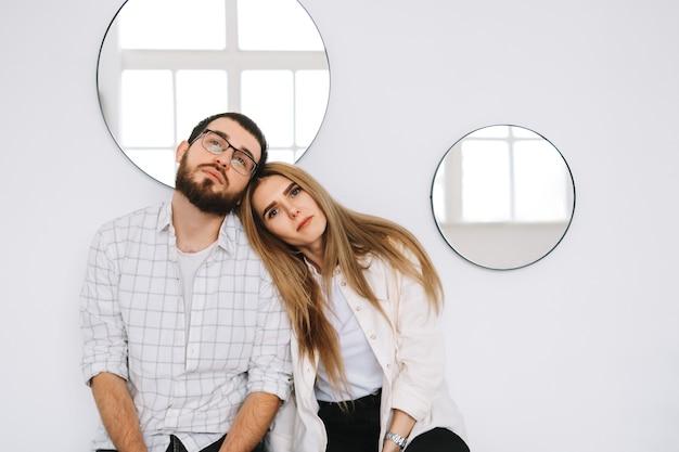 白い壁の近くの自宅のソファに座っている幸せなカップルの肖像画