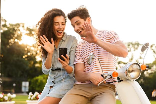 행복 한 커플의 초상화, 도시 거리에 함께 스쿠터에 앉아있는 동안 스마트 폰을보고 이어폰을 착용
