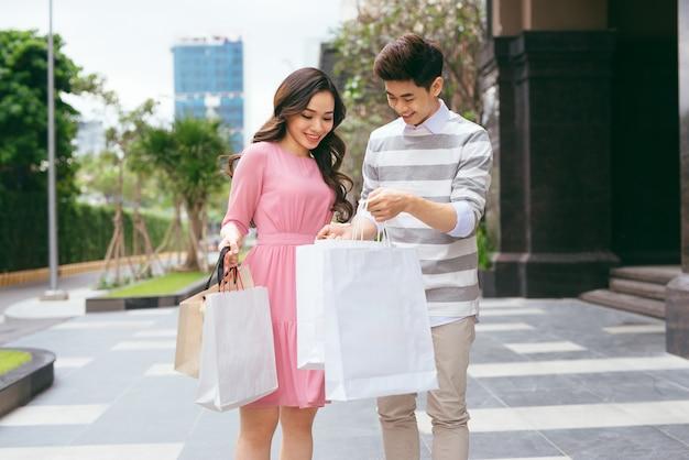 도시에서 쇼핑한 후 쇼핑백을 들고 행복한 커플의 초상화