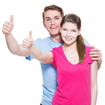 白い壁に分離されたサインを親指で幸せなカップルの肖像画。