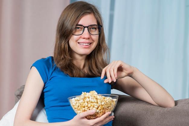 Портрет счастливой плачущей сентиментальной девушки молодой красивой женщины в очках, смотрящей телевизор или драму