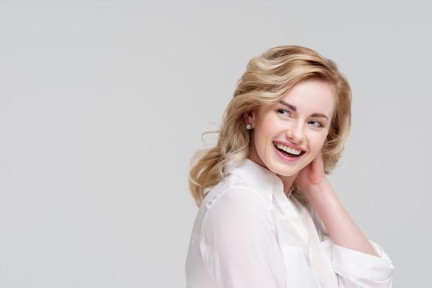 白いシャツで横を探している幸せな巻き毛の女性の肖像画
