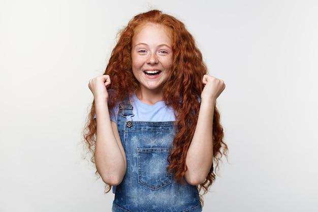 Портрет счастливой милой маленькой девочки с веснушками с рыжими волосами, с поднятыми кулаками, выигравшей коробку конфет, стоит над белой стеной и широко улыбается.