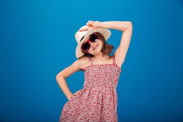 Портрет счастливой милой девушки в шляпе и солнцезащитных очках, позирующей на белом фоне
