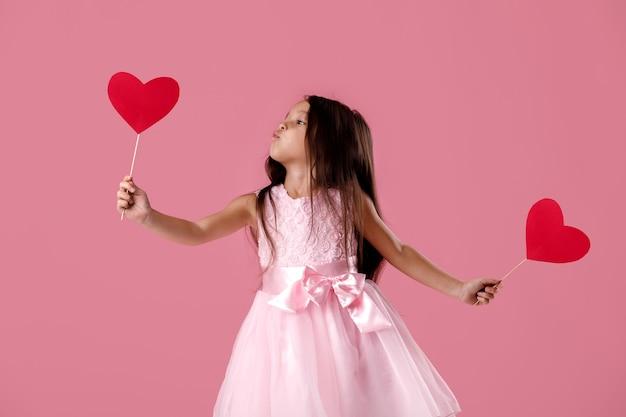 Портрет счастливой милой маленькой девочки в розовом платье с бумажным сердцем