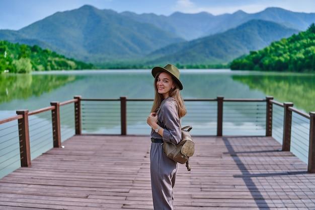 湖と山の景色を望む桟橋に一人で立っている帽子とバックパックを身に着けている幸せなかわいい笑顔の魅力的な放浪者の女の子の肖像画。自然の中で穏やかで静かで平和な雰囲気を楽しんでいます